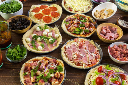 Preparing individual pizzas from pizza bar.