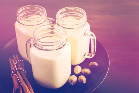 Traditional holiday drink egg nog in drinking mason jars. Stock Photo