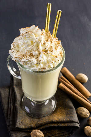 egg nog: Traditional holiday drink egg nog garnished with whipped cream in the glass.