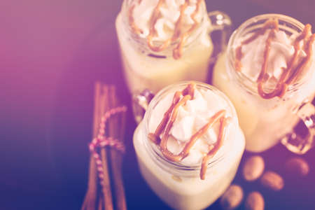 Traditional holiday drink egg nog garnished with caramel and whipped cream in drinking mason jars.