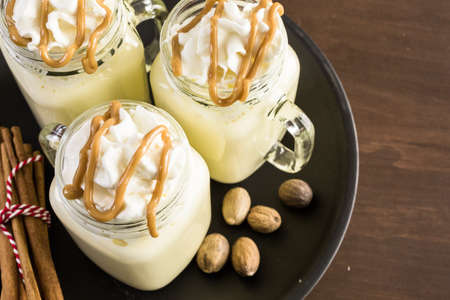 egg nog: Traditional holiday drink egg nog garnished with caramel and whipped cream in drinking mason jars.