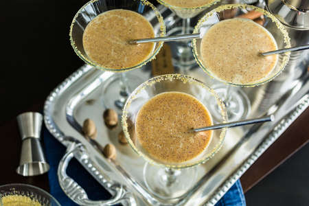 Egg nog cocktail in glasses rimmed with brown sugar at the minibar. Stock Photo