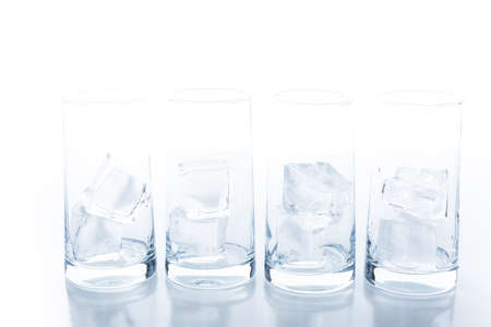 Empty glasses with large ice cubes on a white background.