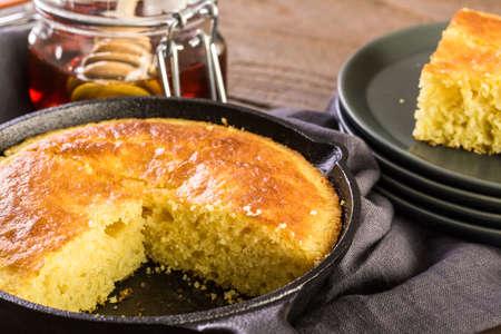 Slice of sweet cornbread with honey on the plate. Фото со стока - 73426366