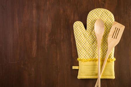 mitt: Yellow oven mitt on wood background. Stock Photo