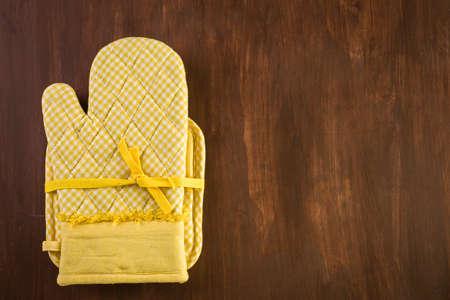 Yellow oven mitt on wood background. Reklamní fotografie