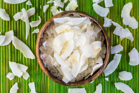 shredded coconut: Dehydrated coconut flakes in wooden bowl.