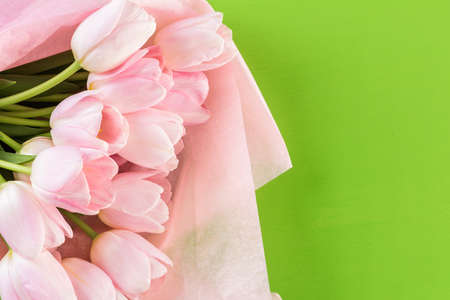 Bouquet of pink tulips wrapped in pink paper.