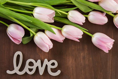 Bouquet of pink tulips on a wood background. Imagens - 73425160