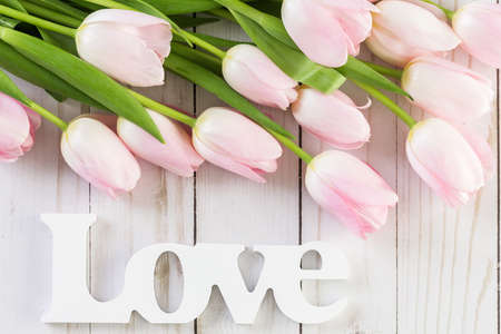 Bouquet of pink tulips on a wood background.