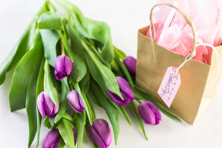 Small gift and purple tulips for Mothers Day. Banco de Imagens