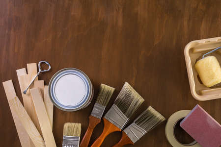can opener: Paint in metal paint can and painters tools on a wood board. Stock Photo