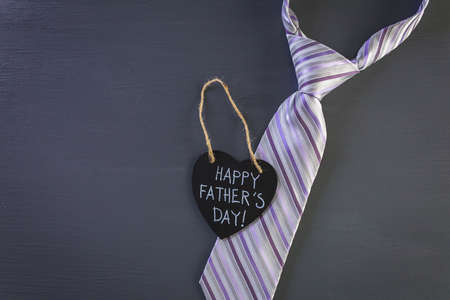 Happy Fathers Day sign on a heart shape chalk board.