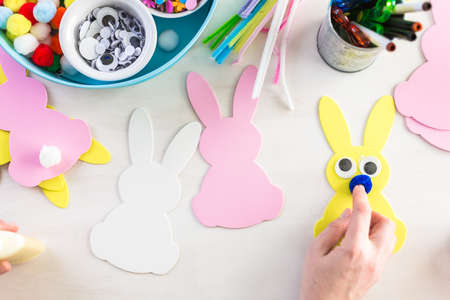 Step by step. Mother and daughter decorating Easter Bunnies.