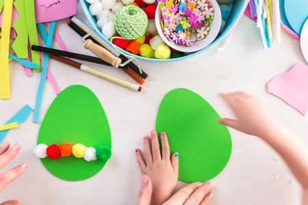 mode made: Step by step. Mother and daughter decorating paper Easter eggs.