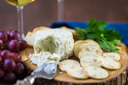 Soft flavored creamy cheese with garlic and fine herbs on a wood board with crackers.