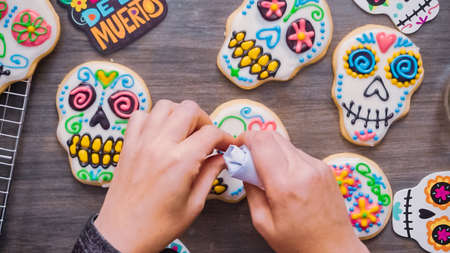 Step by step. Flat lay. Decorating sugar skull cookies with different color royal icing.