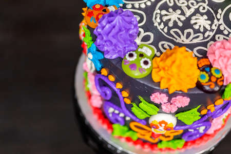 Gourmet Dia de los Muertos cake decorated with colorful buttercream frosting and gummy cupcake toppers.