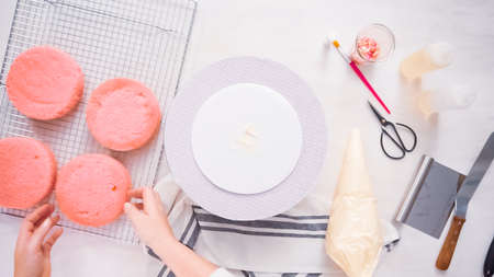 Step by step. Flat lay. Stacking layers together of pink birthday cake.