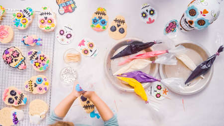 Step by step. Flat lay. Little girl decorating sugar skull cookies with royal icing for Dia de los Muertos holiday. Stock Photo