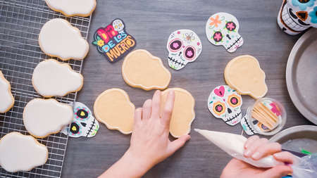 Step by step. Flat lay. Creating edge for flooding sugar skull cookie with royal icing.
