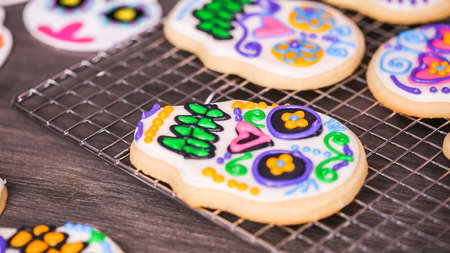 Step by step. Decorating sugar skull cookies with different color royal icing.