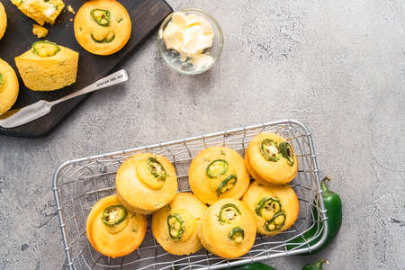Flat lay. Freshly baked cornbread muffins with spicy jalapeno pepper in wired basket.