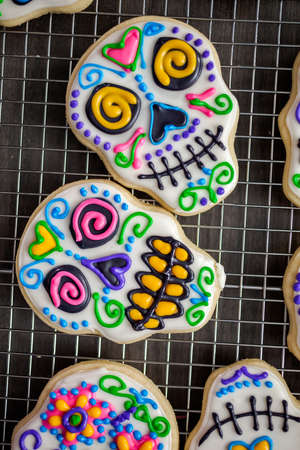 Sugar cookies in shape of sugar skull decorated with colorful royal icing for Día de Muertos-Day of the Dead holiday.