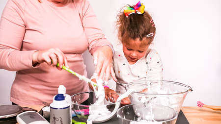 Step by step. Mother and daughter making colorful fluffy slime.