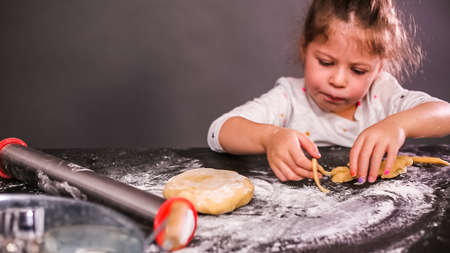 Little girl baking sugar skull cookies for Dia de los Muertos holiday.