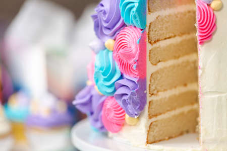 Sliced multilayer unicorn cake on cake stand at the little girl birthday party.