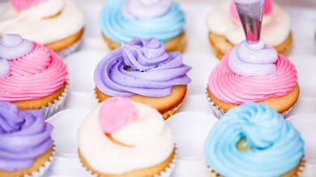 Passo dopo passo. Glassa di crema di burro di tubazioni del pasticcere su cupcakes di unicorno per la festa di compleanno della bambina.
