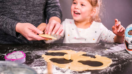 Mother and daughter baking sugar skull cookies for Dia de los Muertos holiday. Stok Fotoğraf