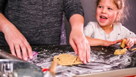 Mother and daughter baking sugar skull cookies for  holiday.