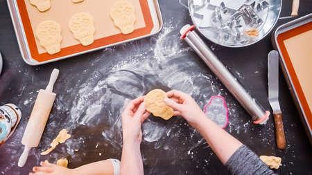 Flat lay. Mother and daughter baking sugar skull cookies for Dia de los Muertos holiday. Stock Photo