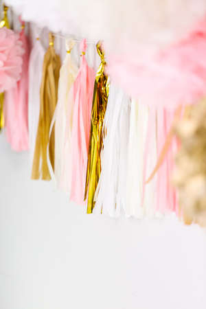 Pink and gold paper tassel garland on the wall at little girl birthday party. 写真素材