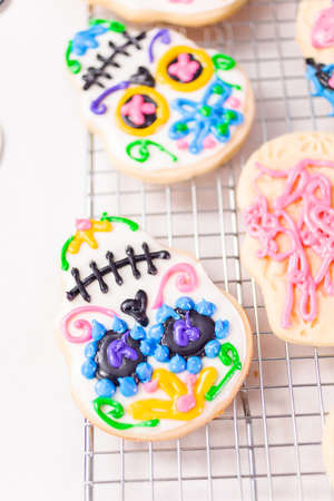 Decorating sugar cookies with royal icing for Dia de los Muertos holiday.