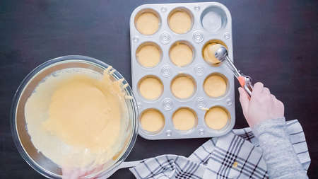Step by step. Top view. Filling metal muffin pan with cornbread batter. Stock Photo