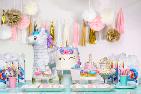 Little girl birthday party table with unicorn cake, cupcakes, and sugaer cookies. Stock Photo