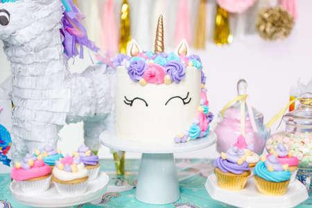Table de fête d'anniversaire de petite fille avec gâteau de licorne, cupcakes et biscuits au sucre.