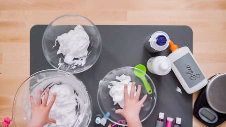 Step by step. Flat lay. Kids project with colorful fluffy slime. 免版税图像