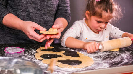Mother and daughter baking sugar skull cookies for  holiday. Stok Fotoğraf - 111779513
