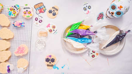 Step by step. Flat lay. Flat lay. Decorating sugar skull cookies with royal icing for Dia de los Muertos holiday.