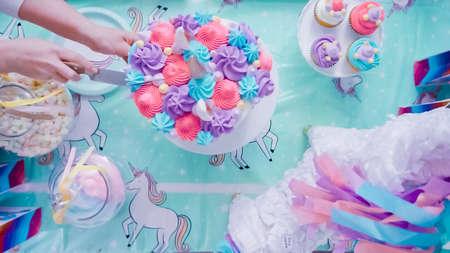 Slicing unicorn cake at little girl birthday party. Stock Photo