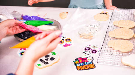 Step by step. Mother and daughter decorating sugar skull cookies with royal icing for Dia de los Muertos holiday. Stock Photo