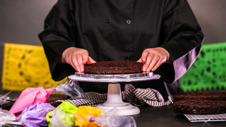 Step by step. Baker assembling a chocolate cake with bright colorful buttercream frosting. 版權商用圖片