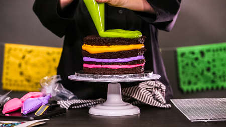 Baker assembling a chocolate cake with bright colorful buttercream frosting. 版權商用圖片