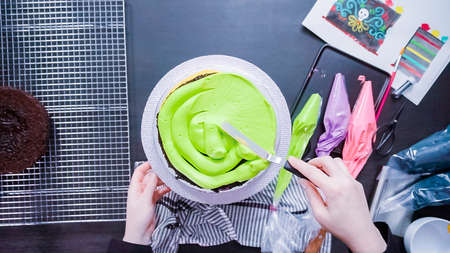 Step by step. Flat lay. Baker assembling a chocolate cake with bright colorful buttercream frosting. Stok Fotoğraf