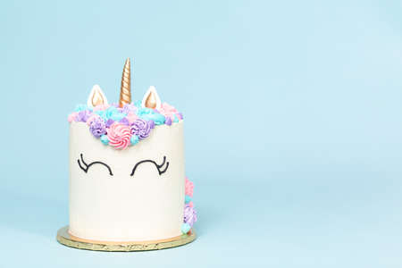 Gourmet unicorn cake with pink and purple buttercream frosting on blue background. Stok Fotoğraf