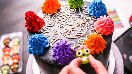 Step by step. Baker piping colorful buttercreal italian icing on a top of multilayer cake for Dia de los Muertos holiday. Banco de Imagens